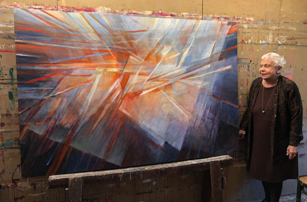 "Rochelle Blumenfeld standing near ""Play of Light"" painting"